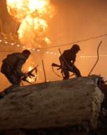 Attraversando un'area aperta, WILLARD e LANCE vengono illuminati dalla battaglia sullo sfondo.