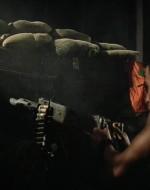 Giungono a una postazione, nella quale DUE SOLDATI DI COLORE sono appostati dietro una mitragliatrice calibro 50. Il MITRAGLIERE spara nel buio della notte imprecando contro i vietcong. L'OSSERVATORE inserisce i proiettili nella mitragliatrice. MITRAGLIERE (al NEMICO) : Ti ho detto di piantarla di rompermi il cazzo! Ti credi un duro, eh, negraccio? // WILLARD : A chi stai sparando, soldato? // MITRAGLIERE : Ai musi gialli! A chi cazzo credi che stia sparando? // OSSERVATORE : Sono tutti morti, idiota. Ne è rimasto vivo solo uno sotto i corpi.