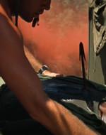 CHIEF continua a guardare WILLARD negli occhi, poi sta per cadere. WILLARD lo prende al volo e viene trascinato sul ponte dal peso del suo corpo.