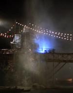 Il ponte è in stato d'assedio. I proiettili di mortai e i razzi solcano la notte a casaccio e penetrano nella giungla vicina. Di tanto in tanto si SENTE IL FUOCO DI ARMI automatiche leggere. L'intera scena è illuminata da razzi paracadute.