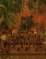 Il tempio. Un magnifico accampamento fortificato eretto attorno alle rovine di un'antica civiltà cambogiana. Le fortificazioni sono fiancheggiate da filo spinato e postazioni di armi automatiche. Nel campo SI VEDONO famiglie, fuochi, dimore di nomadi, CENTINAIA dei più primitivi montagnard. Alcuni sono armati di lance, altri emergono qua e là dalla giungla, affrettandosi per l'agitazione causata dall'arrivo di un estraneo. Nei pressi del pontile giacciono cataste di corpi aggrovigliati e semisommersi nell'acqua, cataste di morti.