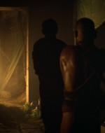 INT. QUARTIER GENERALE DI KURTZ - GIORNO. WILLARD, le mani legate dietro la schiena, viene condotto in un lungo corridoio da due montagnard armati.