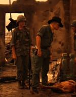 KILGORE : Che succede qui? // SOLDATO : Quest'uomo è gravemente ferito, signore. L'unica cosa che gli tiene dentro le budella, signore, è quel coperchio. // SOLDATO SUDVIETNAMITA : Questo soldato è uno sporco vietcong. Vuole acqua. Può bere acqua di risaia. // KILGORE : Datemi quella borraccia. Un uomo che ha abbastanza coraggio per combattere tenendosi dentro le budella può bere dalla mia borraccia quando vuole. - Si china e comincia a dissetare il prigioniero. Un soldato lo raggiunge di corsa. SOLDATO: Colonnello, credo che uno di quei marinai sia Lance Johnson, il surfista. - KILGORE si rialza abbandonando il prigioniero ferito e restituendo la borraccia. Poi si avvicina a WILLARD e ai suoi.