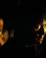 Gli INDIGENI fanno cenno a WILLARD d'inginocchiarsi a terra. KURTZ giace coricato su un letto nella penombra.