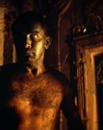 INT. TEMPIO - NOTTE. WILLARD appare dietro una guardia, gli posa una mano sulla bocca, solleva il machete e trascina la guardia all'indietro nel buio.