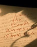 """Sfoglia il manoscritto e si ferma. SI VEDE una frase scritta su una pagina: """"BOMBARDATELI, STERMINATELI TUTTI""""."""