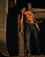 Osservano WILLARD che avanza reggendo il machete e alcuni libri di KURTZ.