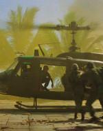 EST. VILLAGGIO - Un piccolo gruppo di elicotteri si abbassa e atterra. I soldati cominciano a saltare giù, corrono cercando riparo sotto una pioggia di proiettili d'artiglieria. Procedono a sgomberare il villaggio dei vietcong, sparando dentro le case. Un soldato spara a una fila di vasi di fronte a una casa. I vasi esplodono. Un soldato di colore viene scaraventato a terra dallo scoppio. E' gravemente ferito. Un elicottero di soccorso atterra accanto al fumo. I soldati trasportano il ferito sull'elicottero. Con gesti frenetici, gli americani spingono due anziani vietnamiti a bordo dell'elicottero per interrogarli.