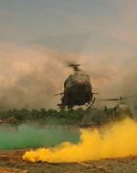 EST. SPIAGGIA - GIORNO. L'elicottero di KILGORE atterra sollevando una nuvola di polvere.