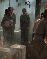 EST. CIMITERO - GIORNO. Il gruppo è al completo. Davanti a una fossa c'è un plotone di soldati cambogiani. I soldati presentano i loro fucili mentre il corpo di CLEAN viene trasportato verso la fossa.