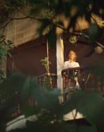 E' una giovane donna vestita di bianco. Sta guardando la cerimonia. Si volta e rientra a casa.