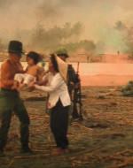 KILGORE si strappa di dosso camicia e foulard. Poi prende fra le braccia un neonato insanguinato retto da una donna vietnamita che fa parte di un gruppo di pregionieri. (a un SOLDATO) : Portatelo via di qui! E dite ai miei ragazzi che voglio la mia tavola!