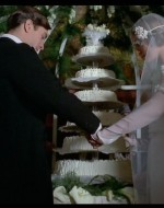 """Stacco. Ricevimento in casa Berlinghieri. Mentre un pianoforte suona la marcia nuziale, Ada e Alfredo stanno davanti alla torta, a ricevere gli applausi degli ospiti insieme al rituale """"Viva gli sposi!""""."""