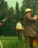 Alfredo si reca con la cesta piena di bottiglie al campo dove lavorano i suoi braccianti.  //  ALFREDO (distribuendo le bottiglie): Basta di lavorare, si beve. Salute a tutti!