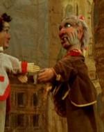 Nell'atrio della stazione è stato montato un teatrino di burattini. Le due marionette, Sandrone e Fagiolino, saltano di qua e di là.