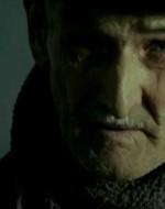 """Un uomo anziano sta finendo di scrivere su un quaderno la frase """"Il comunismo è la giovinezza del mondo""""."""
