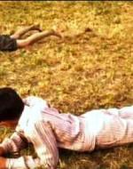 E' sempre Olmo a guidare il gioco. Comincia a scavare la terra con le mani e si sdraia sulla pancia con il sesso in corrispondenza del buco che ha fatto. Incomincia a ondeggiare su e giù. Alfredo lo imita.  // ALFREDO: Ma cosa fai? // OLMO: Inculo la terra.