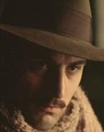 Fuori, nel buio, a qualche metro dalla finestra, c'è Alfredo, immobile nel buio. Non visto, spia al di là dei vetri Ada e Olmo, seduti uno di fronte all'altra. All'interno, Olmo continua a parlare.  // OLMO: Adesso le porte sono aperte. Ma lui non viene più.