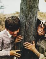 I due corrono verso la strada ferrata. Olmo si avvicina a un palo del telegrafo. Alfredino lo segue.  //  ALFREDO: Che fai adesso? // OLMO (appoggiando l'orecchio al legno per ascoltare le vibrazioni): Sento la voce di mio padre che mi parla… // ALFREDO (imitandolo): Io non sento niente.