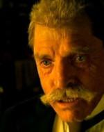 Il vecchio Alfredo si ferma a mangiare a un suo tavolinetto.  //  ALFREDO sr:  C'è un mare di merda fra noi… Fra me e tutti voialtri: un mare di merda. Compra le macchine, lui! E intanto tutto se ne va in malora. Ti ci affetterai le chiappe con quella falciatrice, signor modernista!