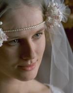 Regina attraversa il salone arrivando di fronte alla sposa. La guarda fissa negli occhi e poi le dà due gran baci sulle guance.