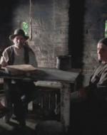 Si mettono intorno a un tavolo sedendosi su oggetti vari: cassette sfondate, il ceppo di un albero.